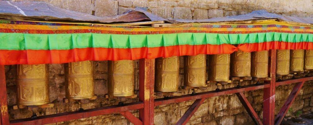My Journey with His Holiness the Dalai Lama - The Wise Traveller - Stationary Prayer Wheels at the Base of the Potala