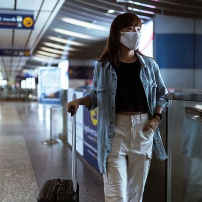 Should You Travel This Year? Questions You Should Ask Before Booking a Trip - The Wise Traveller - Mask and luggage